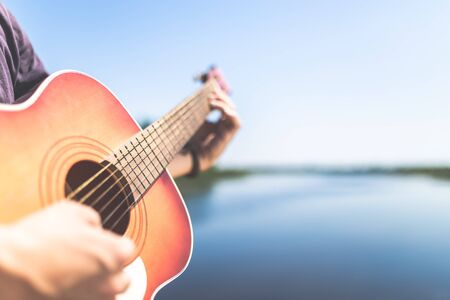 Close up of man playing acoustic guitar against beautiful lake or river and sky. Space for copy.