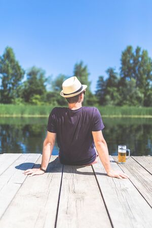 Rear view of hipster man with beer sitting on wooden dock and looking at beautiful lake. 스톡 콘텐츠 - 124984080