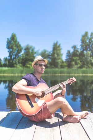 Young hipster guy holding acoustic guitar while sitting on dock in nature. Summer and travel concept.