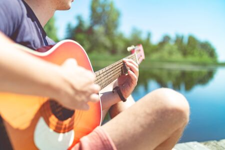 Close up of man sitting on pier and playing acoustic guitar. Beautiful lake in the background. Space for copy.