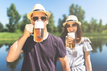 Young couple drinking beer outdoors.