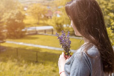 Side view of young woman holding flowers against beautiful nature.