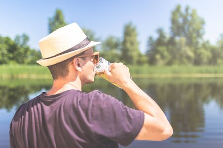 Rear view of young man wearing straw hat and drinking beer against beautiful nature. Imagens