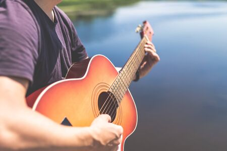Close up of man playing acoustic guitar against beautiful lake or river. Space for copy. Stock Photo