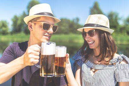 Beautiful couple cheering with beer glasses in nature. Summer vacation and party concept. Imagens - 124984110