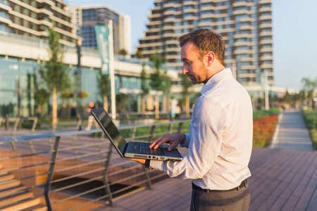 Side view of business professional with laptop outdoors.
