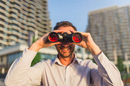 Young businessman watching through binoculars with office buildings in the background.