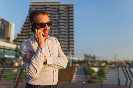 Portrait of successful businessman calling on mobile phone in front of office building.