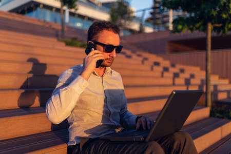 Side view portrait of young business executive calling on smartphone and using laptop outdoors.