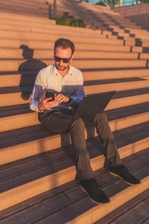 Modern businessman holding mobile phone and laptop while sitting on outdoor steps.