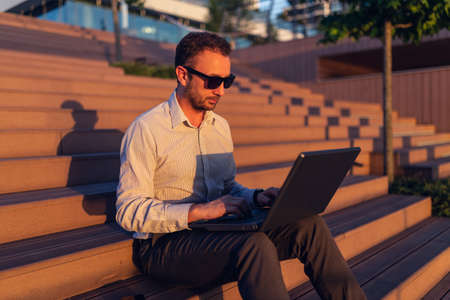 Portrait of businessman using laptop and sitting on stairs outdoors at sunset. 版權商用圖片