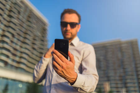 Businessman using touch screen mobile phone outdoors. Stock Photo