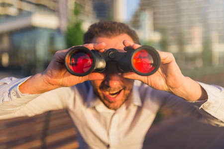 Close up of cheerful businessman with binoculars outdoors.