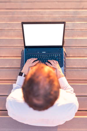 Top view of business professional sitting on wooden steps with hands on empty screen laptop at sunset. Stock Photo