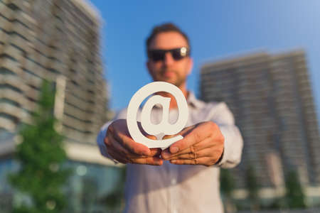 Businessman holding email symbol in front of business buildings. Contact us concept.