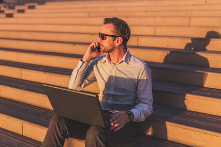 Businessman talking on mobile phone and using laptop while sitting on stairs outdoors.