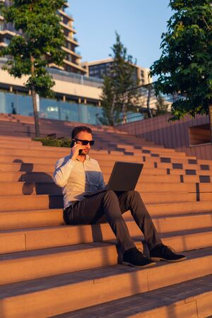 Portrait of successful business person with laptop and smartphone sitting on stairs against modern skyscraper in the background.