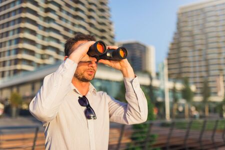 Young businessman looking through binoculars with office buildings in the background.
