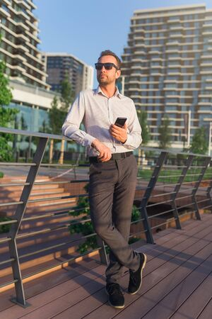 Successful business executive using smartphone outdoors. Office buildings in the background.