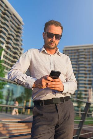 Young caucasian business executive holding smartphone for business work outdoors.
