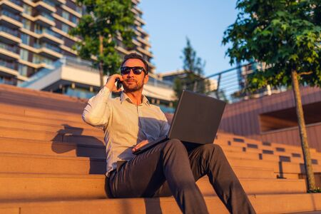 Modern freelancer talking on smartphone and using laptop while sitting on steps in front of business building at sunset.