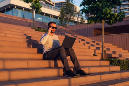 Modern freelancer talking on smartphone and using laptop while sitting on steps at sunset. 스톡 콘텐츠