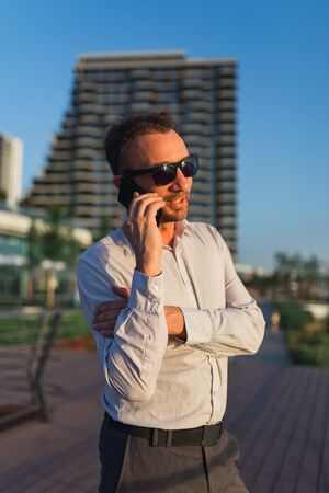 Cheerful businessman talking on smartphone outdoors.