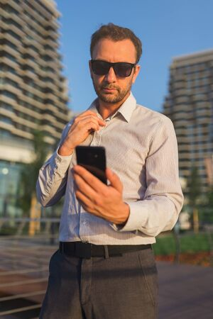 Modern entrepreneur holding and looking at his mobile phone outdoors. 스톡 콘텐츠