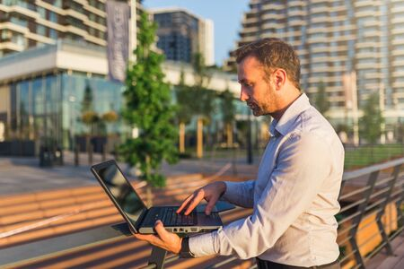 Businessman using laptop in front of office building.
