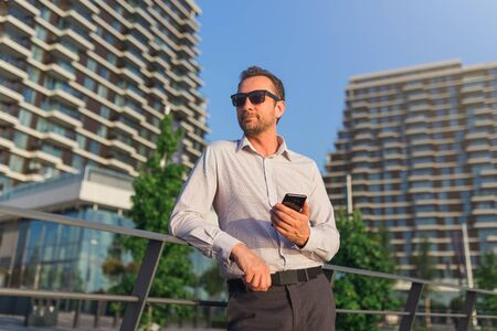 Portrait of modern businessman holding mobile phone against business buildings. 스톡 콘텐츠