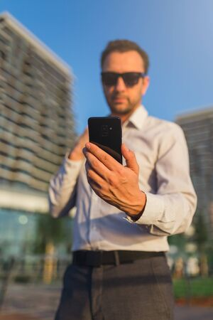 Businessman checking messages on smartphone against office buildings in the background.