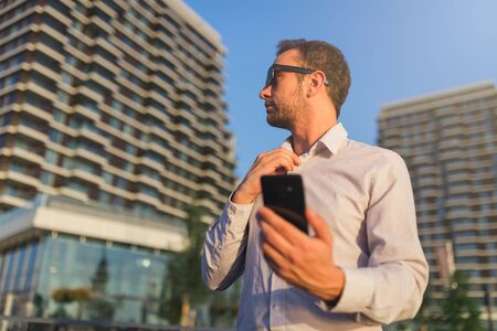 Businessman with smartphone in front of office building.