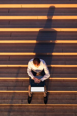 High angle view of businessman sitting on stairs, checking time on his watch and working on laptop at sunset. 스톡 콘텐츠