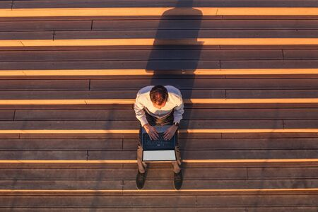 High angle view of businessman sitting on stairs and working on laptop at sunset.
