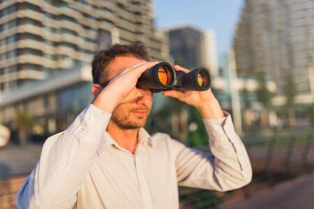 Modern man using binoculars outdoors.