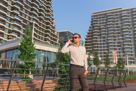 Modern businessman calling on smartphone in front of office buildings.
