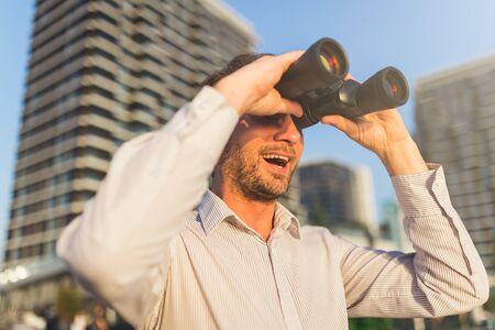Cheerful businessman holding binoculars. Business vision concept. 스톡 콘텐츠