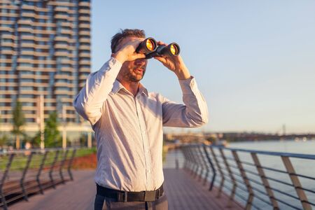 Business person looking through binoculars in front of business buildings. 스톡 콘텐츠