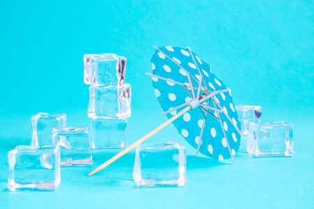 Paper umbrella and ice cubes isolated on bright blue background minimal creative summer and refreshment concept. 스톡 콘텐츠