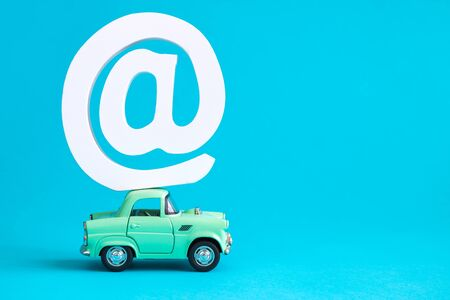 Car toy and email sign against blue background minimal creative concept. Space for copy. 스톡 콘텐츠