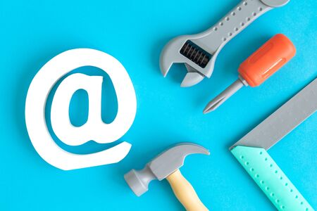 Plastic carpentry tools and email symbol abstract isolated on blue.