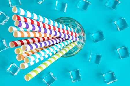 Colorful drinking straws in glass and ice cubes on pastel blue background summer refreshment minimal creative concept.