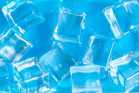 Close up of ice cubes against blue background minimal creative concept.