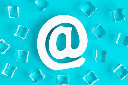 Flat lay of e-mail sign and ice cubes against blue background minimal creative concept.