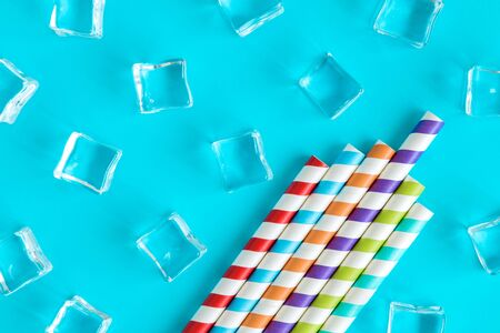 Flat lay of colorful drinking straws and ice cubes against blue background minimal creative summer and drink concept.