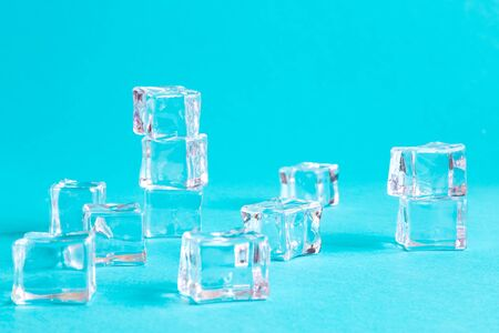 Ice cubes on bright blue background minimal summer drink creative concept.