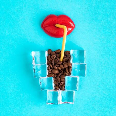 Flat lay of plastic lips drinking ice coffee made of ice cubes and coffee beans minimal creative summer concept.