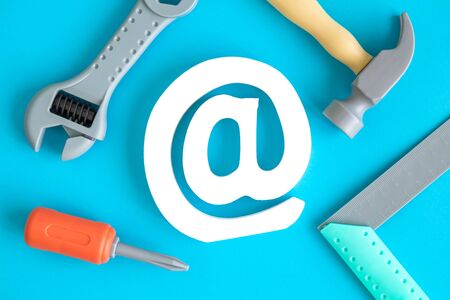Flat lay of construction tool toys and email sign against blue background minimal creative concept. 스톡 콘텐츠