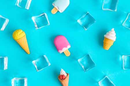 Flat lay of miniature ice cream and ice cubes isolated on blue background minimal summer and food creative concept.