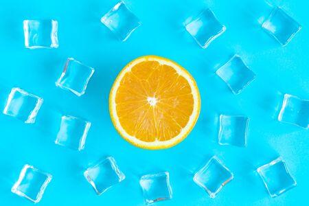 Flat lay of orange fruit slice and ice cubes on blue background minimal creative summer orangeade drink concept.